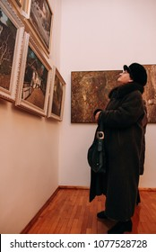Zbarag, Ternopil / Ukraine - February 20 2009: Side view of senior caucasian woman standing in an art gallery in front of colorful framed paintings on a wall