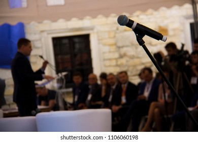 """Zbarazh, Ternopil region, Ukraine - 05.24.2018: Investment Forum """"Ternopil region Invest-2018"""" at Zbarazh castle: microphone on the background of a businessman who speaks to the audience on stage."""