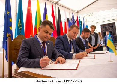 """Zbarazh, Ternopil region, Ukraine - 05.24.2018: Investment Forum """"Ternopil region Invest-2018"""" at Zbarazh castle: businessmen and government officials sign a tripartite agreement (contract)"""