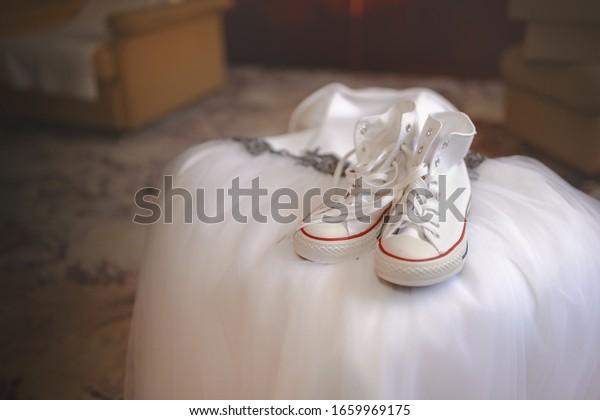 Zbysov, Czech Republic - August 8 2015: Converse shoes lying on wedding dress.