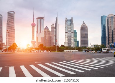 zebra crossing in shanghai century avenue with modern buildings background at dusk