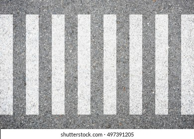 Zebra crosswalk on the road for safety when people walking cross the street.