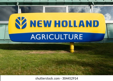 ZEDELGEM, BELGIUM - AUGUST 6, 2015: New Holland Agriculture logo at the factory in Belgium, where the harvesting machines assembly line is located.