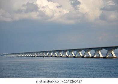 Zeeland Bridge across Oosterschelde estuary in the Netherlands, under a sky with impressive clouds