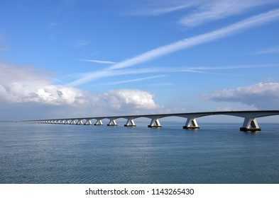 Zeeland Bridge and Oosterschelde estuary in the Netherlands, under a predominantly blue sky with some comulus clouds approaching