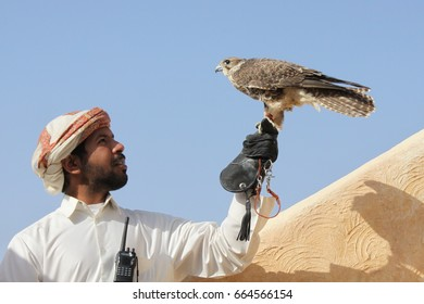 Zekreet - Qatar / December 2010: Man in traditional dress with his pet falcon, classic relation between Arabs and the falcons as they use it for hunting and show