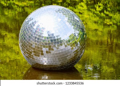 Zelazowa Wola, Poland - June 16 2013: Huge, shine mirrorball in the water. disco mirror ball in the the pond at the park