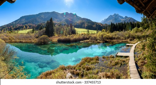 Zelenci lake in Slovenia. Beautiful green lake with mountains and sun in the background. Panorama photo.