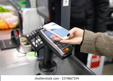 Zelenograd / Russia - 11.10.2019: A female customer hand pays for purchases with a wireless or contactless smartphone payment. Accept payment by NFC technology in a retail store