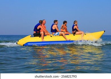 "ZELENOGRADSK, RUSSIA - AUGUST 03, 2014: Sea attraction ""banana boating"", happy people ride the inflatable watercraft banana"