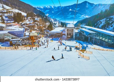 ZELL AM SEE, AUSTRIA - FEBRUARY 28, 2019: Exciting journey on modern cable car with a view on its lower station, skiers on Shcmitten mount pistes, Zeller see and Alps, on February 28 in Zell Am See