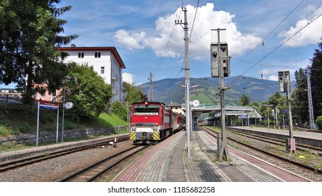 Zell am See / Austria - July 29 2018: A train of the Pinzgauer Lokalbahn at the railway station (bahnhof) of Zell am See in the Pinzgau with beautiful mountains at the background.