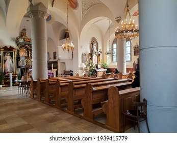 Zembrzyce, Poland - March 2021: Closeup on empty wooden benches in church of Saint John Baptist parish during pandemic of coronavirus. Selected focus.
