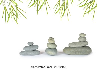 Zen abstract of grey spa stone massage pebbles in perfect balance, with bamboo leaf grass, over white background.
