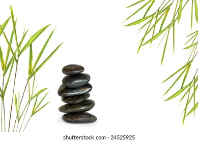 Zen abstract of six black spa massage stones in perfect balance with bamboo leaf grass, over white background.
