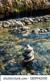Zen art balanced rock stack in stream with hot springs water flow