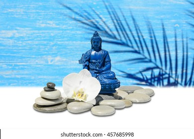 Zen or Feng-Shui background-Blue Medicine Buddha Bhaisajyaguru,zen stone,white orchid flowers.In the background is blurred wooden wall with palm shadow silhouette