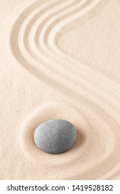 Zen garden meditation stone. Round rock on sandy texture background. Yoga or mindfulness concept.