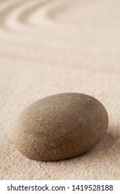 Zen garden meditation stone. Round rock on sandy texture background.