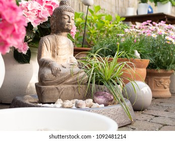 Zen garden with small buddha and flowers, garden decor, yoga background, peaceful scenery, chill out.