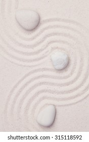 Zen garden with white marble rocks and wave pattern in the white sand