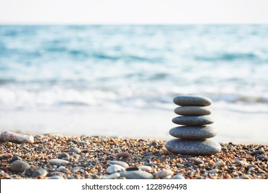 The zen gardens stones on a beach sand. Water waves texture. Spa stones balance pyramid. Place for text.