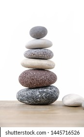 Zen like balanced stone tower isolated on wooden background
