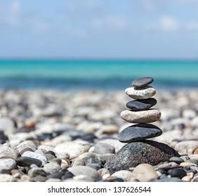 Zen meditation background -  balanced stones stack close up on sea beach