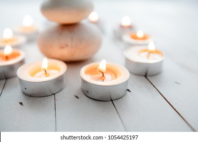 Zen Meditation Harmony, Spa Lifestyle, balanced stack of stones with aromatic candles on wooden white background