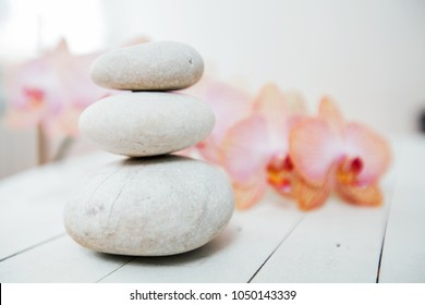 Zen Meditation Spa Lifestyle, balanced stones and flower orchids on white wooden background