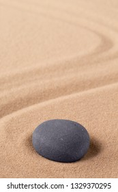Zen meditation stone to focus and concentrate for a quit peace of mind. Spiritual raked sand background texture. Concept for harmony purity and spirituality.