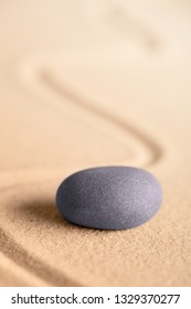 zen meditation stone in a Japanese garden with raked sand. Rock for focus and concentration for balance and spirituality.