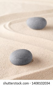 Zen meditation stone in Japanese zen garden. Concept for spirituality, concentration and purity on a minimal sand background.