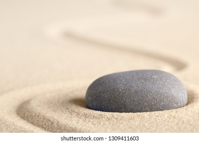 Zen meditation stone with raked line in sand. Concept for harmony relaxation and purity. Spa wellness background