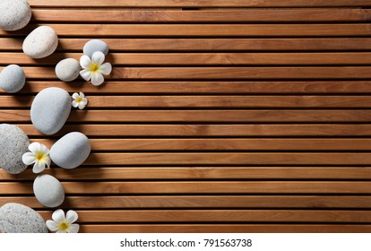 zen pebbles and spa flowers set on hammam wooden board for eco-friendly spa, massage or sauna, copy space still life, above view