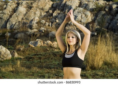 Zen pretty woman practicing exercise tai chi, kung fu or yoga in natural park hands above head