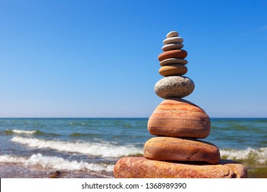Zen pyramid of balanced stones on a background of the summer sea and blue sky. Concept of spiritual harmony, balance and meditation