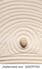Zen sand and stone garden with raked lines, curves and circles with selective focus. Simplicity, concentration or calmness abstract concept. Top view.