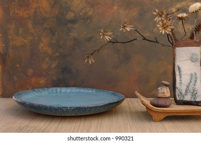 Zen spa still life with Raku vase, natural dried flowers, basin, and stones.