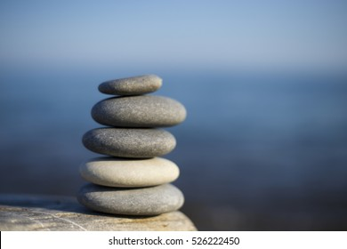 Zen spa stones with blue water and sky. Balanced stones background with copy space. Spa symbol. Beautiful picture. Symbol of stability.