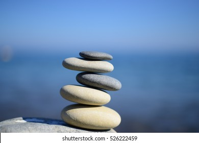 Zen spa stones with blue water and sky. Balanced stones background with copy space. Spa concept. Beautiful picture. Symbol of stability. Stones pile background. Stone balance. Tranquil, sustainability