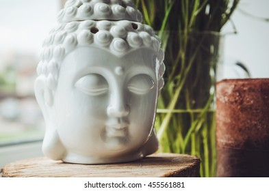 Zen spiritual ritual meditating white face of Buddha on green floral background. Religion concept, esoterics. Still life, rustic style. Home decor. Place for text, copy space