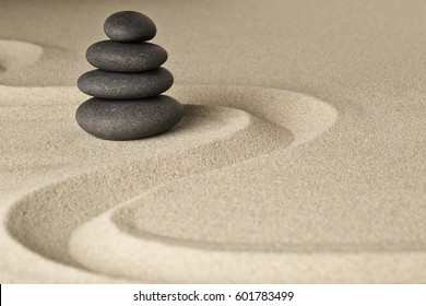 Zen stone balance and harmony, a pile of dark black stones stacked in a Japanese sand garden.