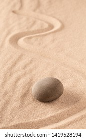 Zen stone Japanese meditation sand garden for focus and concentration on balance and spirituality. Yoga or spa wellness sandy background with round rock and open copy space.