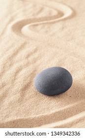 Zen stone Japanese sand garden round rock in sand. Buddhism or yoga background for spiritual purity and concentration.