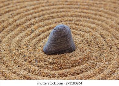 Zen stone on raked sand
