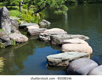 Zen stone path in a Japanese Garden across a tranquil pond with carps and turtles
