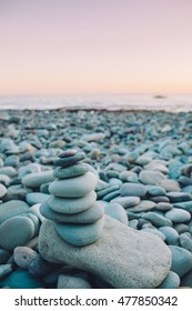 Zen stone tower made of blue stones on the beach. Meditation in yoga retreat. Asia, Indonesia, Flores.