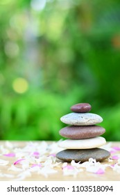 Zen stones and fallen flowers on wooden left space position with green leaves vertical background.