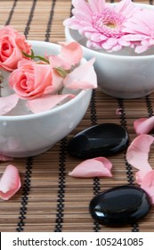 Zen stones with flowers on a bamboo pad, spa and healthcare concept